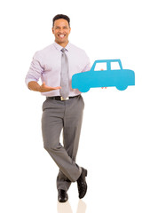 mid age man presenting paper car