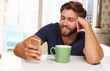 Young Man Drinking Coffee And Using Mobile Phone At Home - 80825334