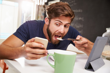 Man Eating Breakfast Whilst Using Digital Tablet And Phone