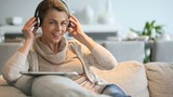 Smiling mature woman listening to music with tablet