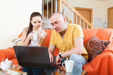 Man and woman at  laptop at  coffee table