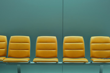 Row of empty orange chairs against gray wall