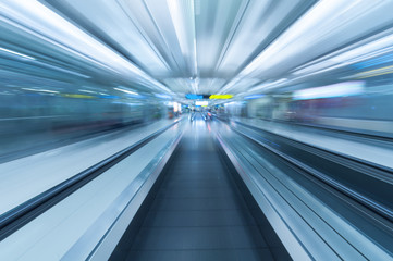 Blurred movement along airport walkway