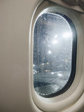 Airplane window view at night with raindrop perspective