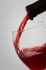 Bottle filling the glass of wine. Splash of wine