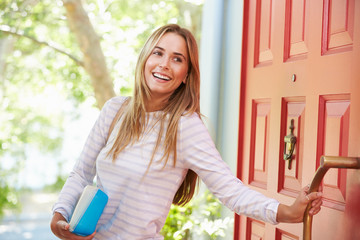 Young Woman Leaving Home For Work With Packed Lunch