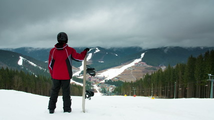 The man with snowboard stand, watch and rest