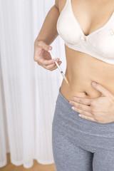 Junge Frau spitzt sich Insulin oder Heparin, Diabetes