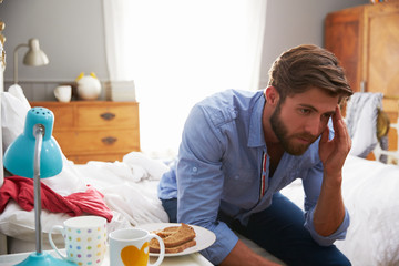 Man Suffering From Depression Sitting On Edge Of Bed