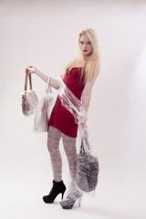Junge Frau mit langen blonden Haaren und drei Handtaschen