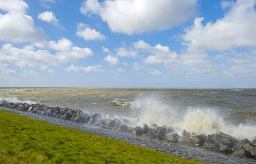 Storm raging over a lake along a dike in spring