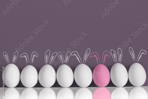 Pink bunny among white rabbits as Easter eggs - 80833738