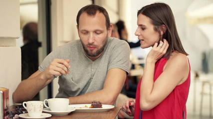 Couple meeting in cafe in city, talking and eating cake