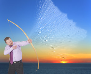Businessman practicing archery on sunset background