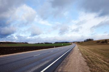 Cloudy landscape with asphalt road, Latvia, Europe.