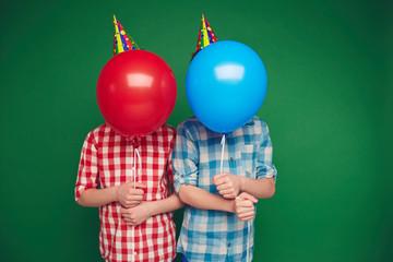 Boys behind balloons