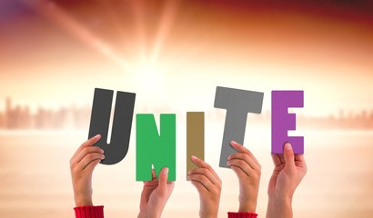 Composite image of hands holding up unite