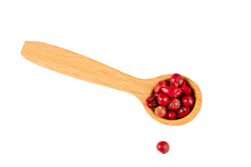 red peppercorns in a spoon over white