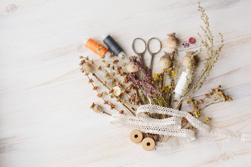 Sewing kit with flowers on a wooden background
