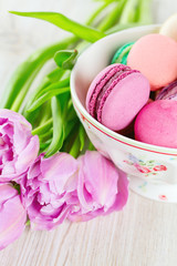 colorful macarons and tulips on wooden surface