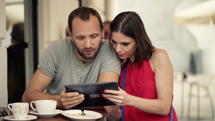 Couple talking and using tablet computer standing in cafe
