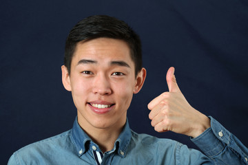 Smiling young Asian man giving the thumbs up sign and looking at