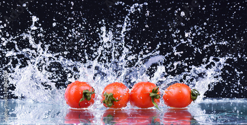 czerwone pomidory czereśniowe z pluskiem wody