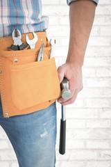 Handyman wearing tool belt while holding hammer