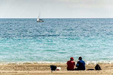 2 Männer sitzen am Strand im Sand