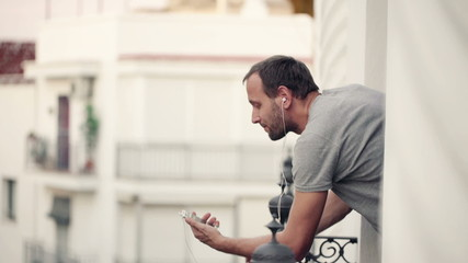 Young man listen to music on cellphone standing on balcony