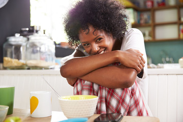 Portrait Of Young Woman Eating Breakfast In Kitchen