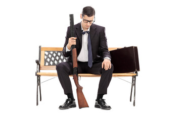 Depressed businessman holding a shotgun rifle