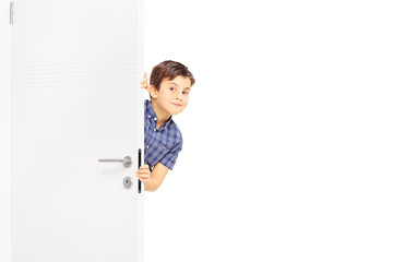 Lovely little boy sneaking a peek behind a door