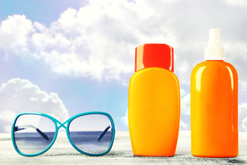 Bottles with suntan cream with sunglasses