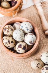 raw quail eggs in a wooden bowl on burlap background
