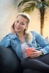 Blonde Frau sitzt auf dem Sofa und trinkt Kaffee