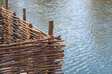 decorative wicker fence on the background of water