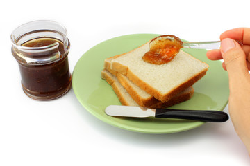 Hand spreads jam on fresh bread