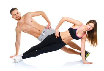 Attractive sport couple - man and woman doing fitness exercises
