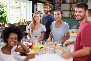 Group Of Friends Cooking Breakfast In Kitchen Together