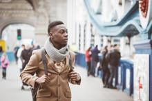 """Постер, картина, фотообои """"Young black man in London walking on Tower Bridge"""""""