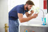 Fototapety Man In Pajamas Brushing Teeth And Using Mobile Phone