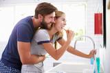 Couple In Pajamas Brushing Teeth In Bathroom