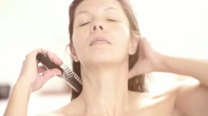 Freundliche Frau bürstet ihre feuchten Haare