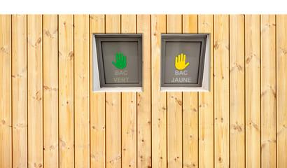 poubelles de tri sélectif derrière palissade bois