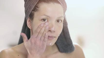 Glückliche Frau trägt Gesichtscreme auf