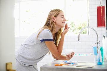 Woman In Pajamas Putting On Moisturizer In Bathroom