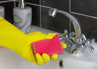 Hand in protective glove washing  tap with rag at bathroom