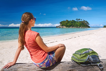 Traveller with backpack relaxing on coast and looking to island