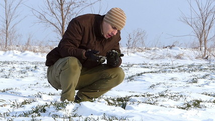 Young farmer checking on wheat in winter.